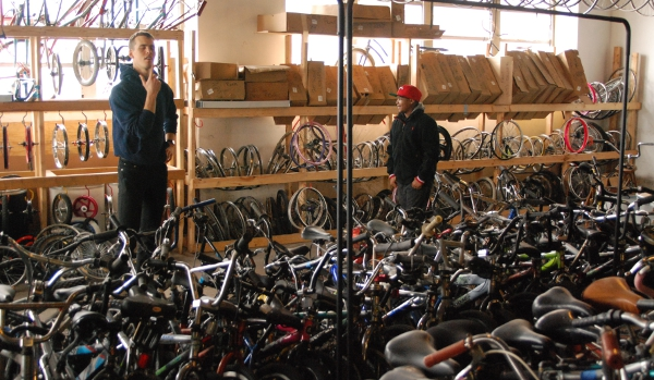 Ham (left) helps Maurice (right) pick out a bike from the warehouse to build up and earn.